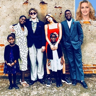 celebrities with twins 6 children of different ages posing together with an inset of Madonna's headshot in the top right corner