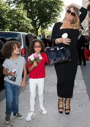 celebrities with twins Mariah Carey holding a bag and a flower while standing on a crowded sidewalk with her twins