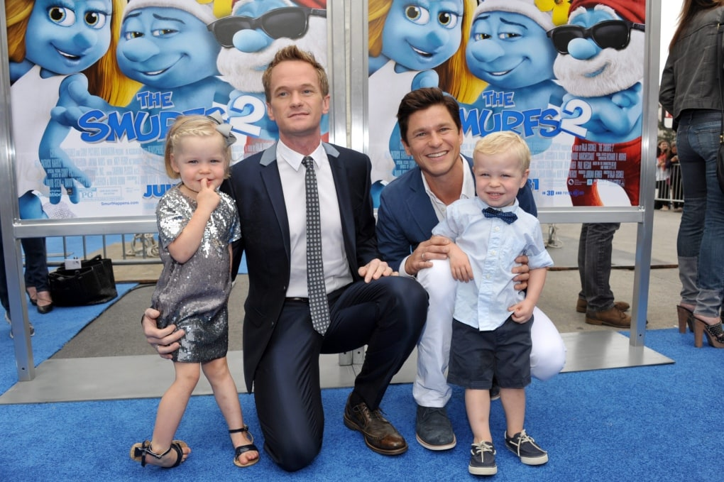 celebrities with twins Neil Patrick Harris and David Burtka posing with twin boy and girl on a blue carpet in front of a Smurfs movie poster