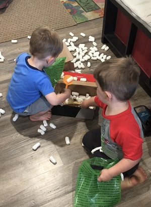 naughty list toddler boys playing with packing peanuts and bags
