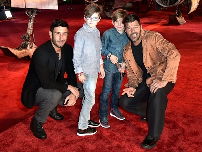 celebrities with twins two men (Martin and Yosef) kneeling down and posing with young twin boys on a red carpet