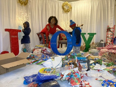 highlights of 2020 a woman smiling with 2 boys in a room with wrapping paper and the word JOY in glitter letters