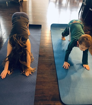 indoor physical activities 2 young kids doing yoga on mats