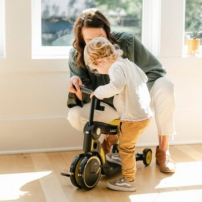 toddler scooter a woman holding a scooter to help a toddler step on in a house