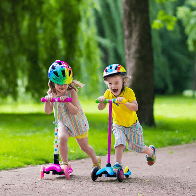 toddler scooter a little boy and a little girl riding on scooters in a park