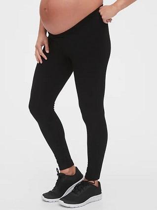 maternity leggings a pregnant woman wearing balck leggings and black tennis shoes