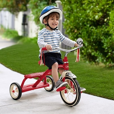 A boy on the sidewalk wearing a helmet riding a toddler tricycle
