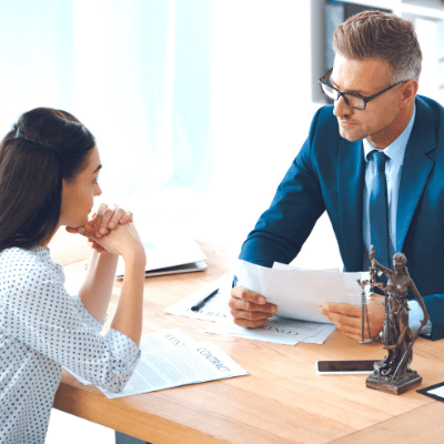 surviving divorce a woman meeting with a lawyer and going over papers together