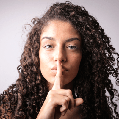 surviving divorce a woman making a shh sign with her finger to her lips