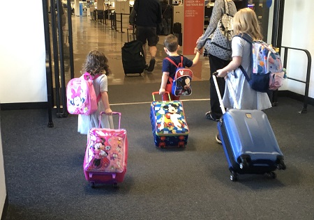 different parenting a woman holing a little boys hand, a little girl and an older girl, all pulling suitcases and wearing backpacks in an airport
