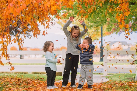 different parenting 3 young kids playing in falling leaves