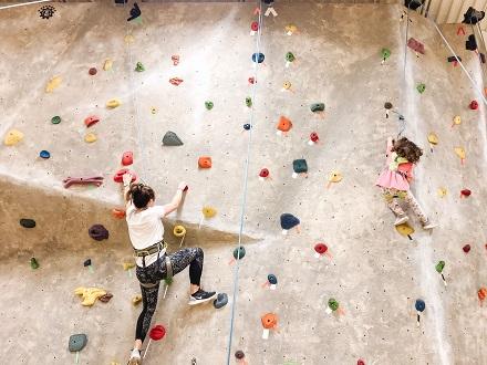 destructive kids a woman and child climbing a rock wall