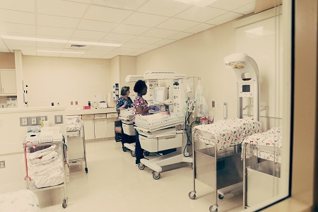 birth trauma a nursery with 2 nurses attending to infants and medical equipment