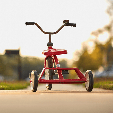 A red tricycle on a sidewalk outside