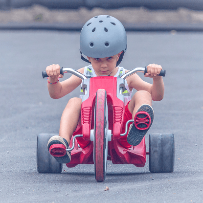 A little boy with a helmet on a toddler tricycle
