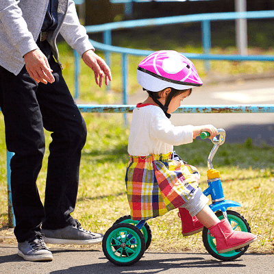A little girl with a pink helmet on a blue tricycle.