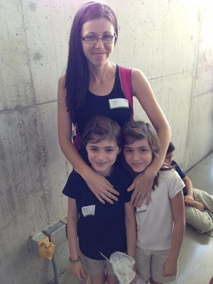 a woman standing with her arms around twin girls smiling for a picture