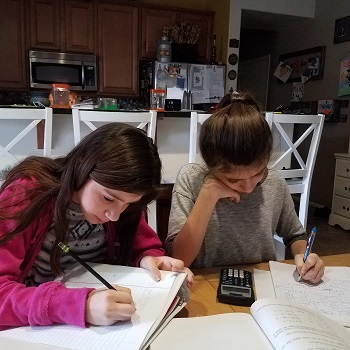 twin girls doing homework at a table together