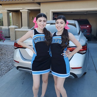 identical twin girls in cheer uniforms with bows posing in a driveway