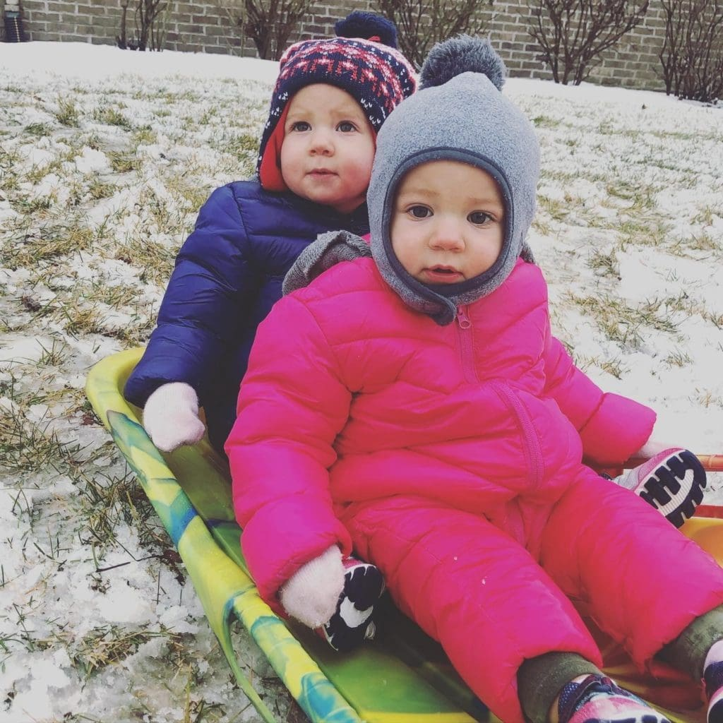 15-month-old identical twin girls on a sled in snow with snowsuits, hats, and mittens on.