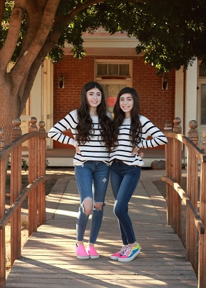identical twin girls wearing matching white ad black stripes sweaters posing for a picture