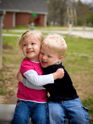 boy girl twins hugging each other sitting outside