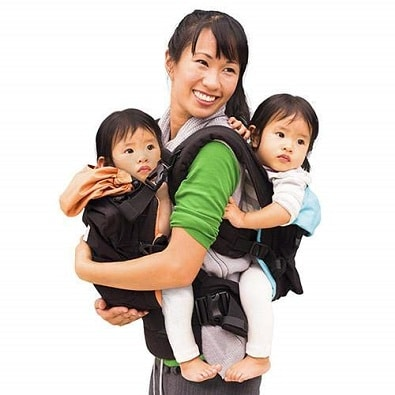 woman holding infant twins in twin baby carriers, one in front, one in back