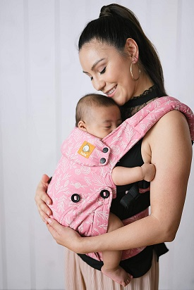 A woman cradling an infant in a front carrier
