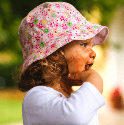 toddler in a pink hat with messy face and hand