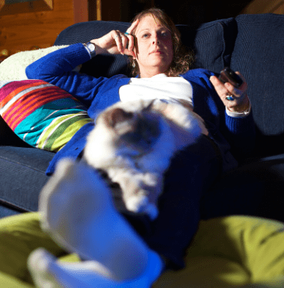 woman lying down watching tv with her cat