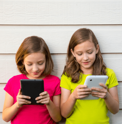 twin girls playing on tablets together