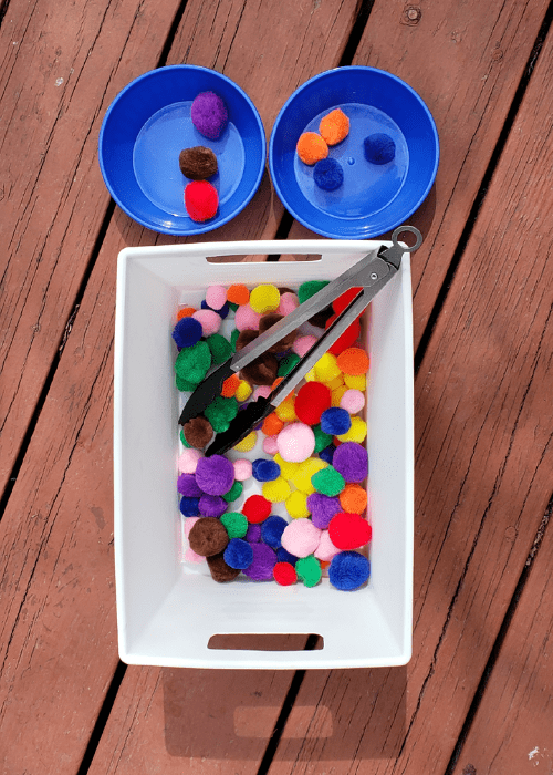 bin with pom poms and tongs with 2 cups for sorting