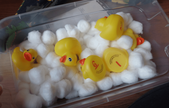 bin with cotton balls and rubber ducks