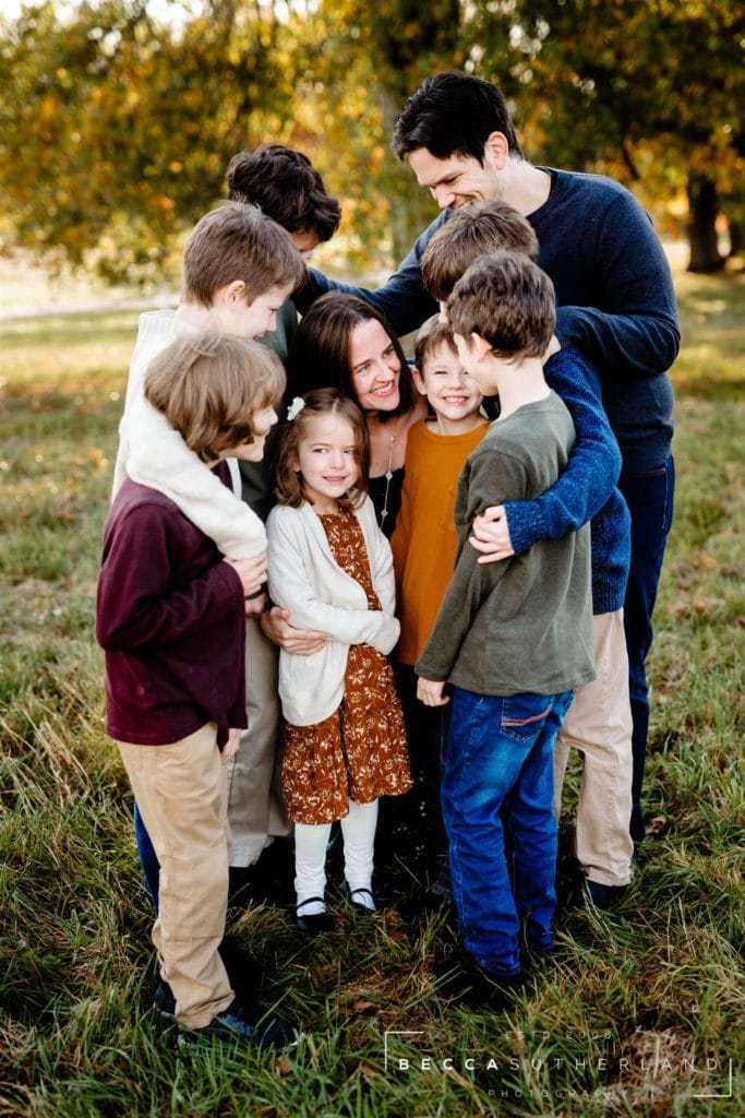 A family of 9 hugging and smiling at each other outside