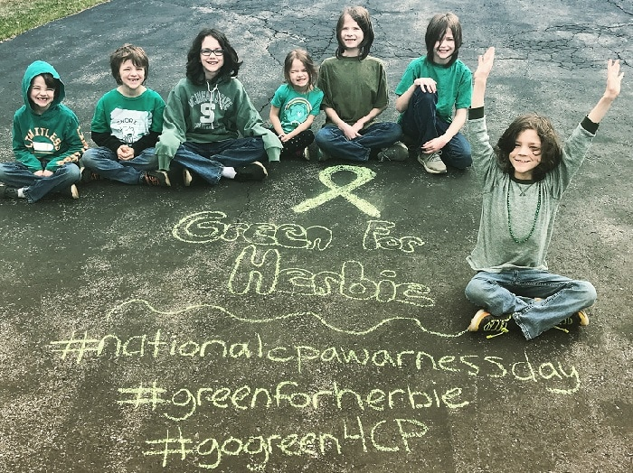 7 kids sitting on pavement