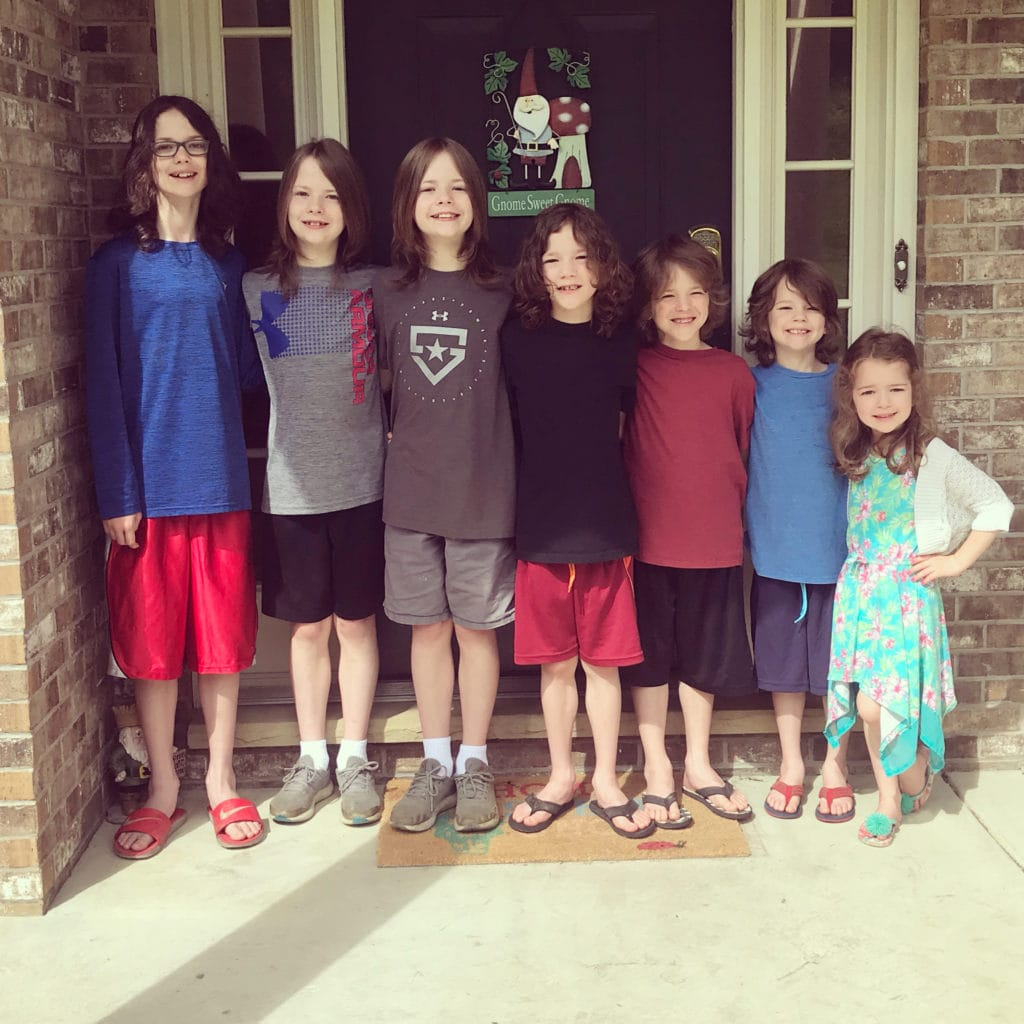 7 children, 6 boys and a girl posing side by side outside a home front door