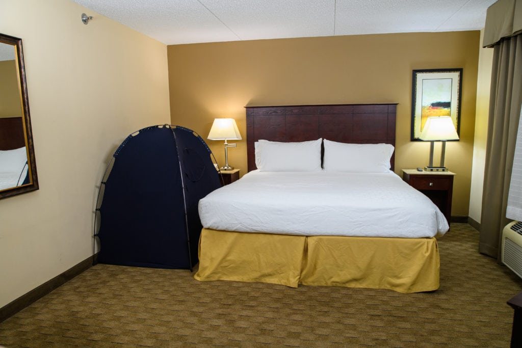 queen bed in a hotel room with a slumberpod