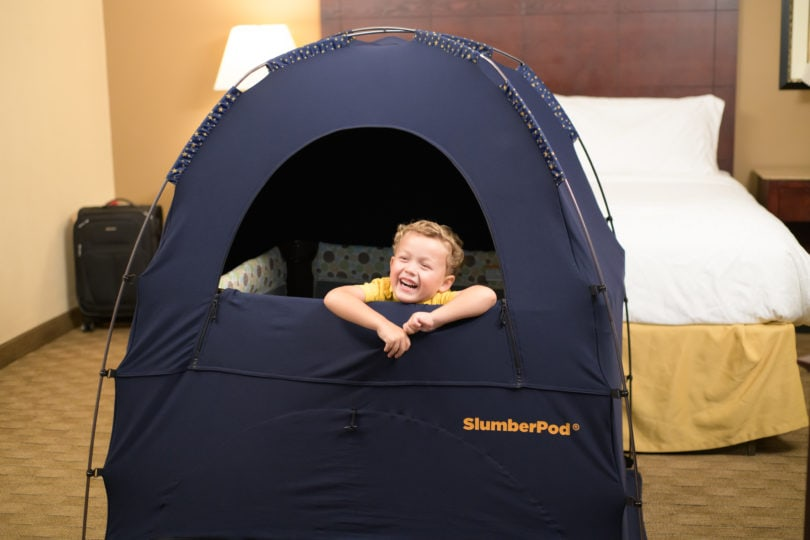 child in a slumberpod over a travel crib in a hotel room