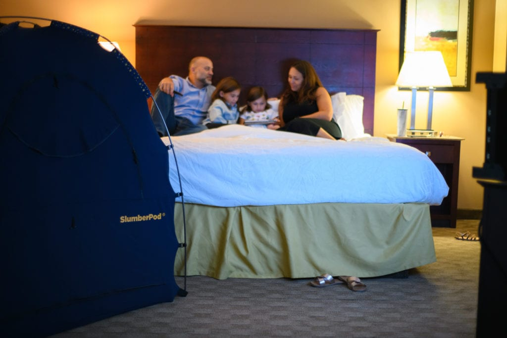 family in a hotel bed with a slumberpod on the side