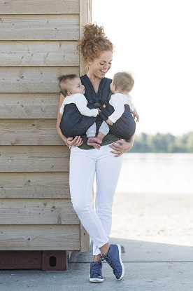 a woman smiling at her infants in a twins baby carrier