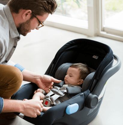 man buckling baby in car seat