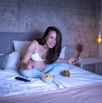 woman sitting in bed laughing while watching tv and eating chips twin pregnancy confessions