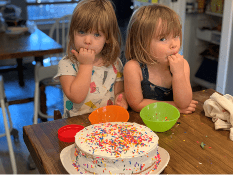 toddler girls licking sprinkles off their fingers