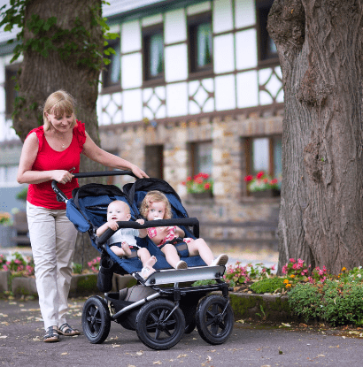 a woman pushing 2 kids in a stroller outside