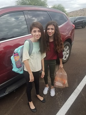 twin girls standing outside with backpacks and school supplies