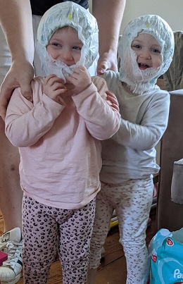 twin toddler laughing with diapers on their heads