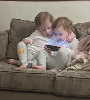 twin girls looking at a phone together on a couch