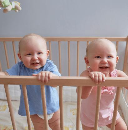 boy girl twins standing in a crib