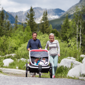 couple pushing double stroller on gravel