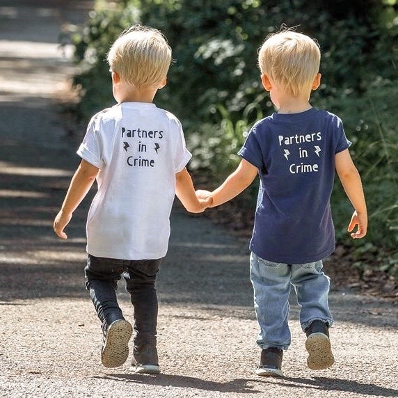twin boys holding hands and walking outside